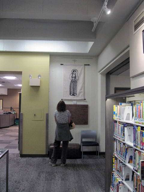 A library patron contemplates La Penitente, which hangs in the hall to the community room